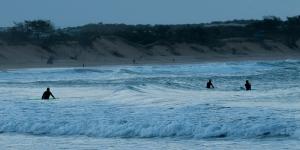 Tre surfisti in riva al mare